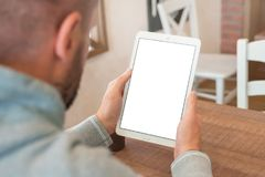 Closeup tablet in man hands. Vertical position. Isolated screen for mockup presentation.  Stock Image