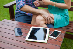 Closeup of tablet, smartphones on the table near sitting couple. Stock Images
