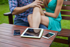 Closeup of tablet, smartphones on the table near sitting couple. Royalty Free Stock Image