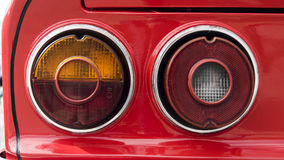 Closeup of the tail lights of a classic car. Closeup of the tail ights of a red classic car royalty free stock image