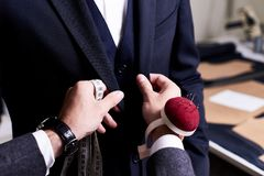 Tailor Pinning Custom Suit. Closeup of tailor fitting bespoke suit to model, hands with tape measure and pin cushion fixing jacket on male model Stock Photo