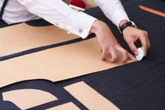 Tailor Tracing Patterns on Cloth. Closeup of tailors table with male hands tracing fabric making pattern for clothes in traditional atelier studio Stock Image