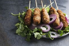 Closeup of tasty cooked lyulya kebab on pile of cilantro and sliced shallot on dark table,rustic style and mood stock images