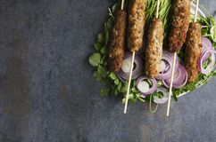 Top view of kebab with onion rings,fresh cilantro served on dark table.Empty space royalty free stock photo