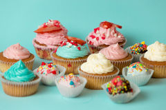 Closeup of tasty freshly baked cupcakes and colorful candies ove Royalty Free Stock Photography