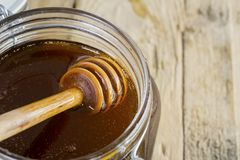 Tasty honey with wooden dipper Royalty Free Stock Image