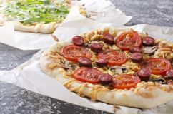 Closeup of tasty hot pizza with tomatoes, cheese, slices of grilled sausages, mushrooms and second one with arugular, different ki stock photography