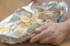 Closeup of tasty roasted carp fish in foil.Chef preparing roasted fish to serve dish royalty free stock photo