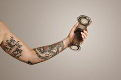 Closeup of tattooed man`s hand holding aeropress Royalty Free Stock Images