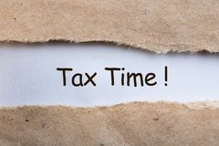 Closeup of Tax Time written on yellow paper note in a torn envelope. Tax planning and budgeting concept Stock Photos