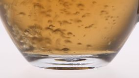 Closeup. Tea is poured into a glass cup. Tea is poured into a glass cup, delicious fragrant black tea for breakfast, glass cup is poured black tea small jet, the stock video