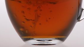 Closeup. Tea is poured into a transparent cup. Tea is poured into a transparent cup, delicious fragrant black tea for breakfast, glass cup is poured black tea stock footage