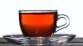 Closeup. Tea spoon stir the drink in a glass cup. Tea spoon stir the bracing drink in a glass cup, teapot from transparent glass is poured black tea, saucer stock footage