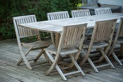 Teak garden furniture on a wooden terrace in spring royalty free stock image