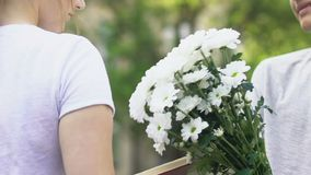 Closeup of teen boy giving flowers to girl, tender first love in adolescence. Stock footage stock video