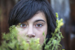 Closeup teen girl with expressive eyes, hidden in the greenery of the garden. Emo. Closeup of black-haired teen girl with expressive eyes, hidden in the Royalty Free Stock Photo