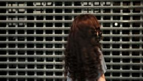 Closeup of teen girl look back and applause in front of metal fence