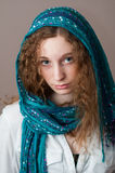 Closeup of a teen girl wearing a headscarf. Beautiful Caucasian teen girl with blue eyes wearing a beautiful blue headscarf Royalty Free Stock Photos