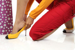 Closeup of a teenage girl removing her heels. After shopping with shopping bags Royalty Free Stock Images