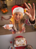 Closeup on teenage girl in santa hat showing candie in kitchen Royalty Free Stock Photos
