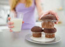 Closeup on teenager girl with milk taking muffin Stock Images
