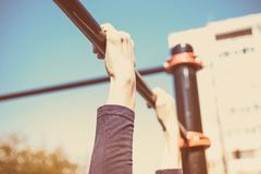 Closeup of a teenager`s hands on a horizontal bar. Pulling on the crossbar. Vintage toning stock photo