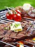 Steak grilling over a fire Stock Image