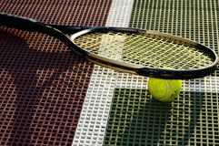 Closeup Tennis. A closeup view of a tennis ball and racquet on the baseline of a tennis court Stock Photo