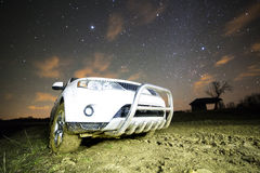 Closeup of terrain car in a countryside landscape with muddy road Stock Image