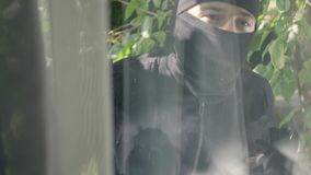 Closeup of the thief in black clothes and balaclava looking in the window preparing to break into the house. Concept of. Close-up of the thief in black clothes stock video footage