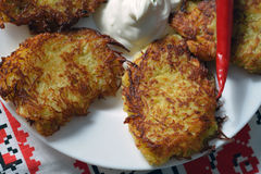 Closeup of thin potato pancakes with hot papper and sour cream Royalty Free Stock Photography