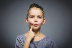 Closeup Thoughtful girl with Hand at head isolated on Gray royalty free stock photography