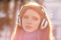 Closeup of thoughtful pretty young lady in headphones Royalty Free Stock Photography