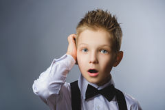 Closeup Thoughtful Young Boy Looking Up with Hand on Face Against Gray Background Royalty Free Stock Photography
