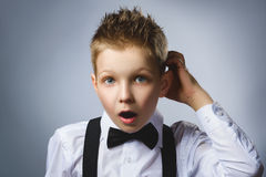 Closeup Thoughtful Young Boy Looking Up with Hand on Face Against Gray Background Stock Image