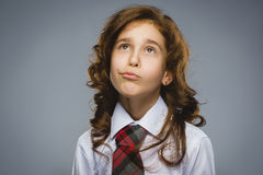 Closeup Thoughtful Young girl Looking Up Against Gray Background Royalty Free Stock Image