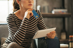 Closeup on thoughtful young woman with credit card Royalty Free Stock Image