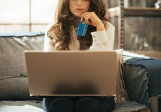 Closeup on thoughtful young woman with credit card Stock Photography