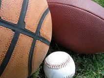 Closeup of three balls. A football, basketball, and baseball on the grass royalty free stock photos