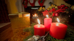 Closeup of three burning candles and golden Christmas gift box at living room stock video footage