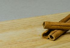 Closeup of three cinnamon sticks. On a wooden cutting board Stock Photography