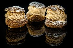 Closeup three french dessert shoo served on black. Closeup three french dessert shoo with caramel cream filling served on black mirror background with reflection royalty free stock photography