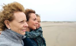 Three generations female looking at sea. Closeup of three generations female looking at sea on the beach in autumn. Background focus on young women and child Royalty Free Stock Photo