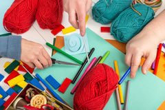 Closeup with three hands and a lot of handicraft materials Royalty Free Stock Image