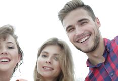 Closeup of three young people smiling on white background Royalty Free Stock Images
