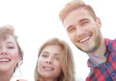 Closeup of three young people smiling on white background. Closeup of three happy young people smiling over white background Stock Images
