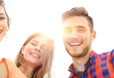 Closeup of three young people smiling on white background. Closeup of three happy young people smiling over white background Royalty Free Stock Photos