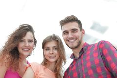 Closeup of three young people smiling on white background. Closeup of three happy young people smiling over white background Royalty Free Stock Photo