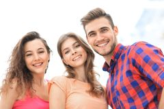 Closeup of three young people smiling on white background. Closeup of three happy young people smiling over white background Stock Image