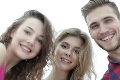 Closeup of three young people smiling on white background Stock Images
